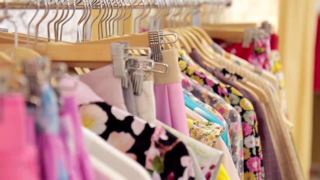 Movimiento de rack con perchas y ropa en tienda - vídeo