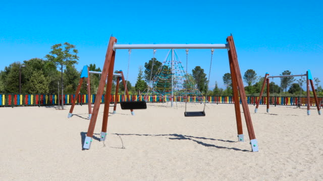 motion shot approaching double empty swings swinging in playground - due oggetti video stock e b–roll