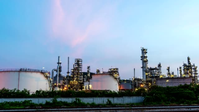 Motion Time lapse. Refinery and oil tank at dusk. Business and petrochemical plants, oil storage tanks and for energy and steel pipes in Twilight time video
