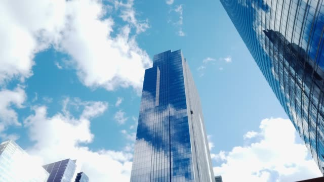 Video 4K UHD Motion time-lapse of buildings in business district with fast moving cloud in sunny day. Financial economy, construction industry, or modern company organization concept