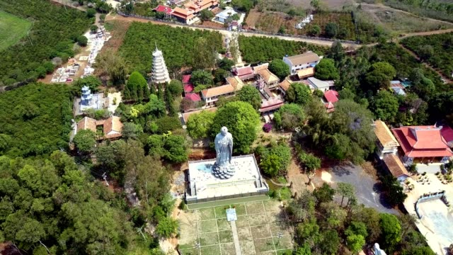 motion to grey Buddha statue situated near monastery upper flight to huge grey Buddha statue situated near monastery buildings among tropical plants sri lankan culture stock videos & royalty-free footage