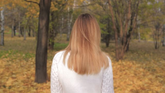 Motion View Back Of Woman Walking, Turns Around, Joyful Smiling In Autumn Park video