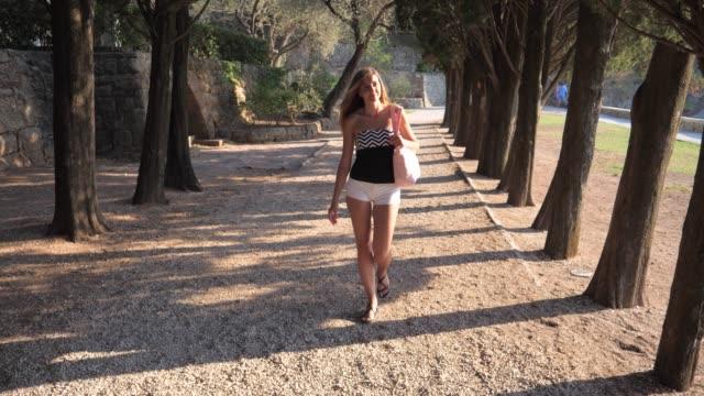 vídeos y material grabado en eventos de stock de movimiento joven atractivo turístico recorriendo árboles callejón en sombras 4k - moda playera