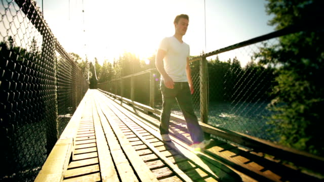 Motion-Photo (Cinemagraph) of a Young Man Crossing a Solid Hanging Bridge over River video