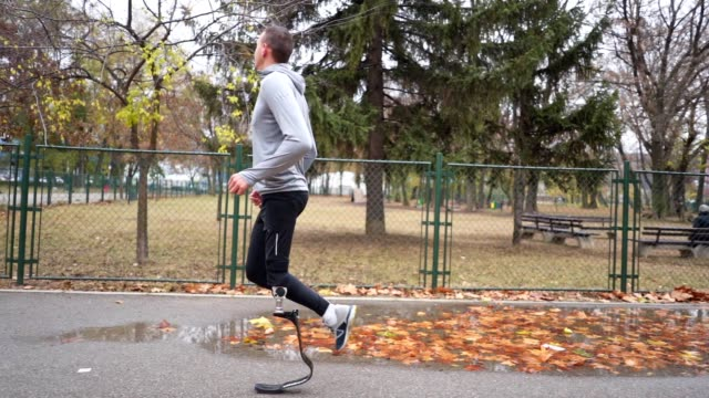 Motivated amputee athlete running outdoors after rain Young and athletic man with a artificial leg, exercising outdoors, living a healthy lifestyle recovering. artificial limb stock videos & royalty-free footage