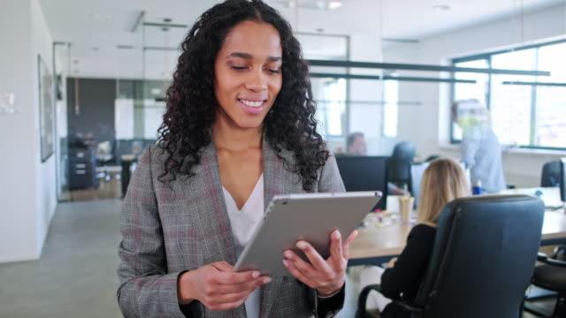 motiverad affärskvinna med digital tablett på kontoret - bekymmerslös bildbanksvideor och videomaterial från bakom kulisserna