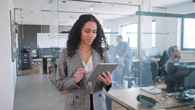 Motivated Businesswoman Walking Through the Office and Using Digital Tablet
