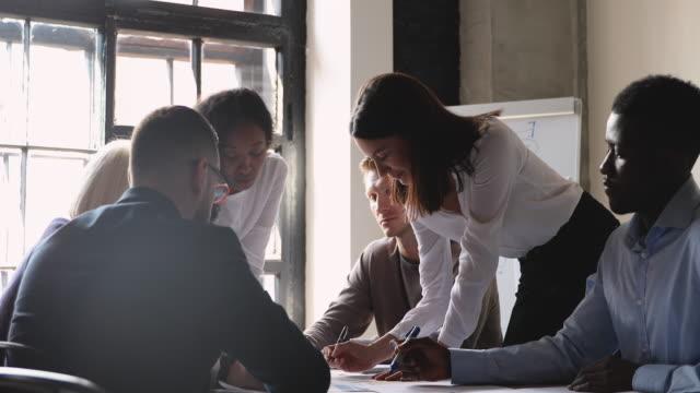 vídeos de stock e filmes b-roll de motivated diverse employees brainstorming at office meeting. - promoção emprego