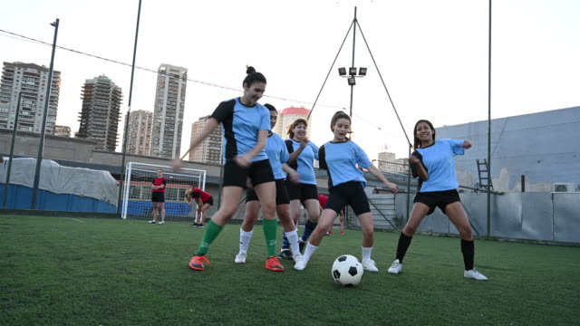 Motivated Hispanic female footballers dancing on field