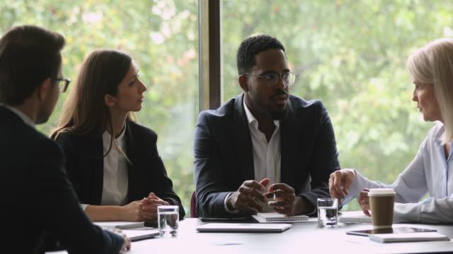 stockvideo's en b-roll-footage met gemotiveerde gemengde race zakenmensen bespreken project op brainstorming meeting. - marketing planning