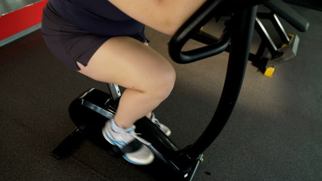 Motivated plump girl pedaling fast at exercise bike in the gym, active workout video