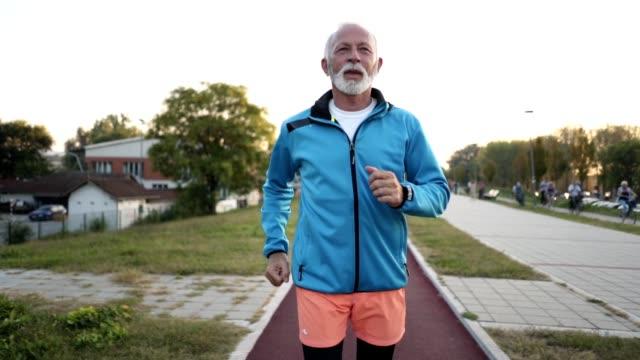 Motivated senior man jogging on a running track