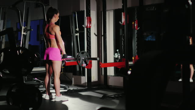 Motivation and commitment to the sport: athletic woman training in a gym in the spotlight. Female bodybuilding video