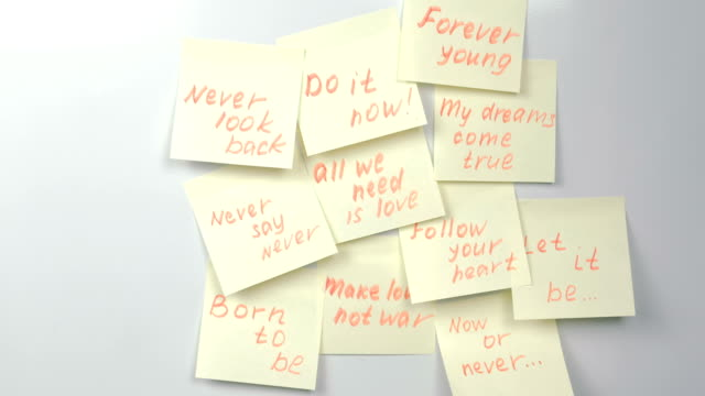 Motivation phrases on yellow sticker paper sheets on a white board. video