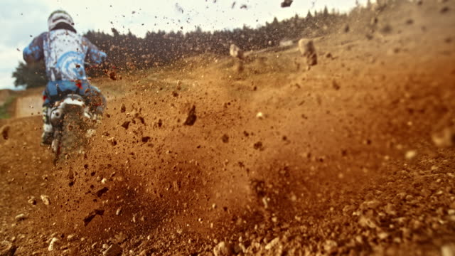 slo mo motocross bike landing in gravel blasting stones around - motocross video stock e b–roll