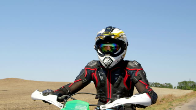 Motocross biker riding enduro motorcycle on country road video