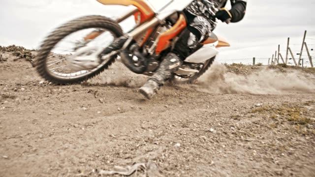 slo mo motocross biker speeding through the turn - supercross video stock e b–roll