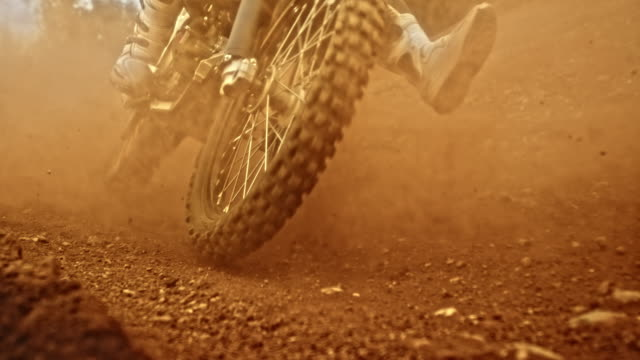 slo mo motocross bikes being ridden through a turn - motocross video stock e b–roll