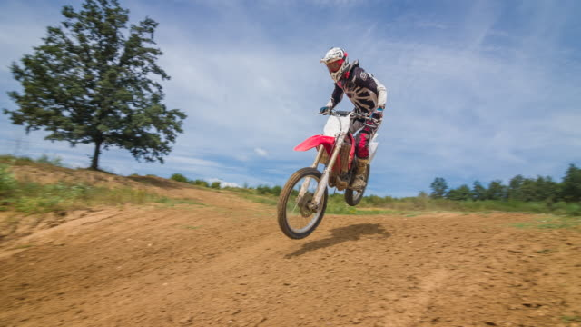 motocross racer jumping on dirt track - motocross video stock e b–roll