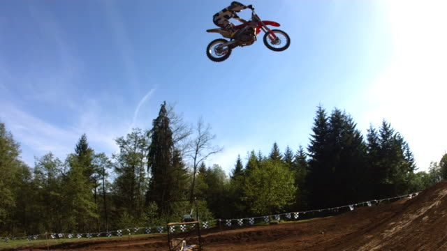 Motocross racer soars over large jump, slow motion video