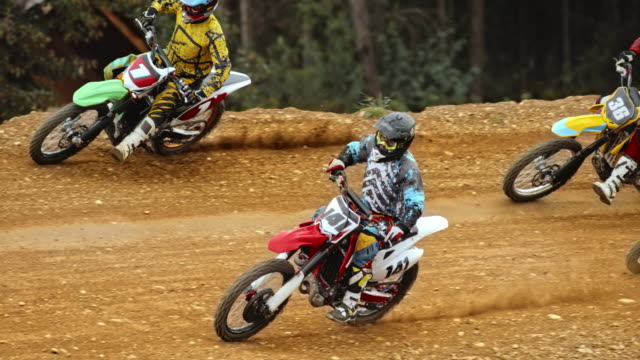 slo mo motocross racers on dirt track - motocross video stock e b–roll