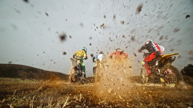 slo mo motocross racers taking off and bursting gravel - motocross video stock e b–roll