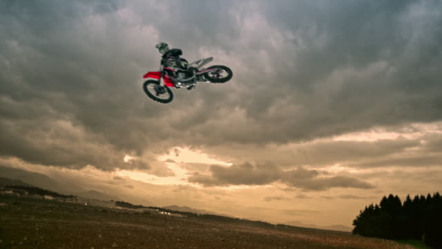 slo mo motocross rider jumping at sunset - motocross video stock e b–roll