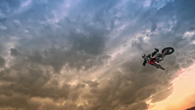 slo mo motocross rider jumping into air at sunset - motocross video stock e b–roll