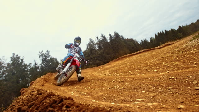 ld motocross rider riding through a turn on dirt trail - motocross video stock e b–roll
