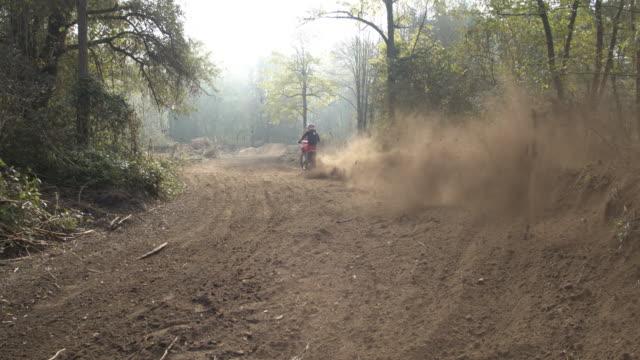 MS Motocross rider sliding, riding on dirt course