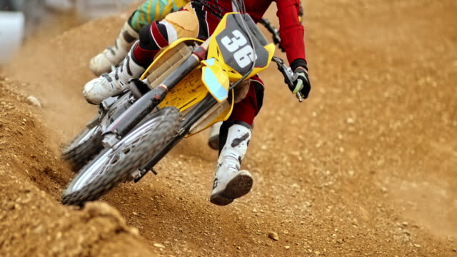slo mo motocross riders racing on a dirt track - motocross video stock e b–roll