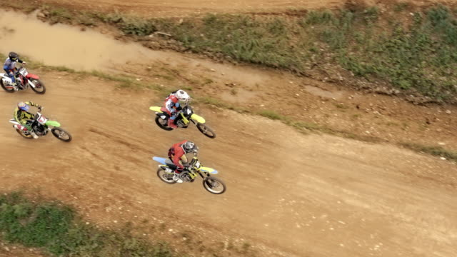 aerial motocross riders racing on dirt trail - motocross video stock e b–roll