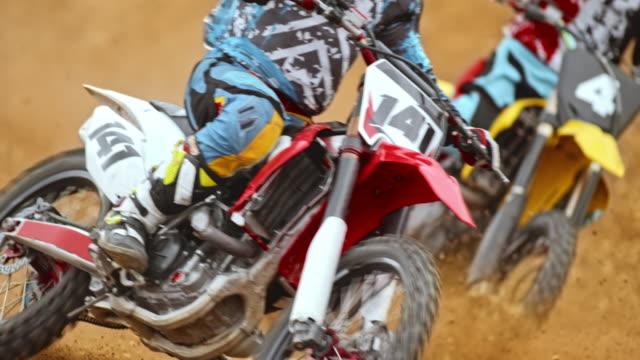 slo mo motocross riders riding on dirt track - motocross video stock e b–roll