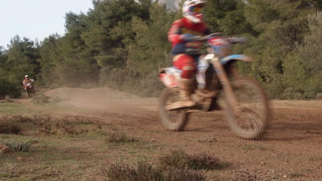 Motocross sports and practice at the forest, a motocross athlete is performing a jump with his motorbikes while two others passing by video