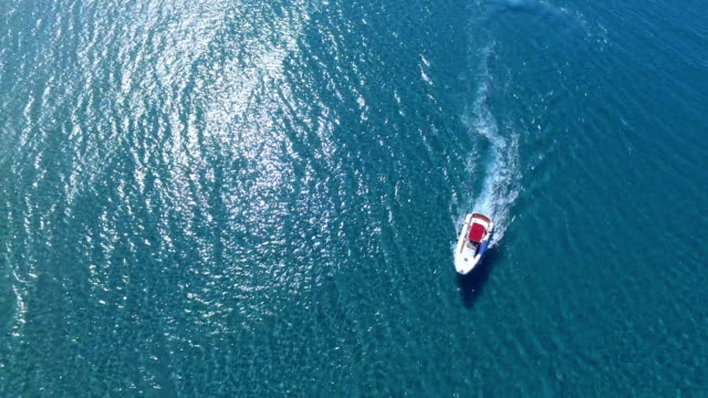 Motor boat cruising along the ocean or sea coast in circles on a sunny day. video