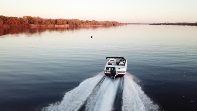 vídeos de stock, filmes e b-roll de barco de motor que flutua no rio no por do sol - veículo aquático