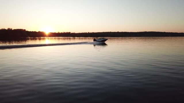 barca a motore galleggiante sul fiume al tramonto - acqua dolce video stock e b–roll