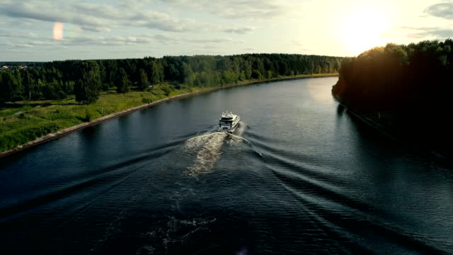 A motor boat floats on the river to the sunset video
