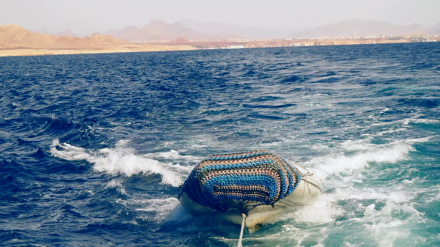 A motor boat is tied with a rope to a floating yacht video