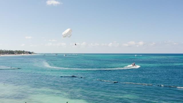Motorboot zieht weißen Fallschirm über das karibische Meer – Video