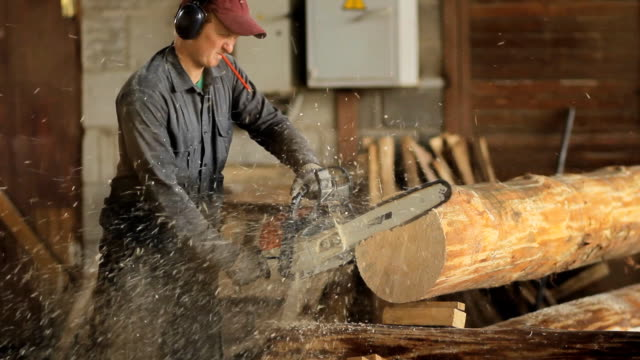 Motor chainsaw cutting wooden beam. Man work with wood house video