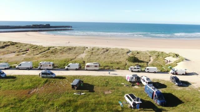 stockvideo's en b-roll-footage met campers en camper wagens geparkeerd door een strand - caravan