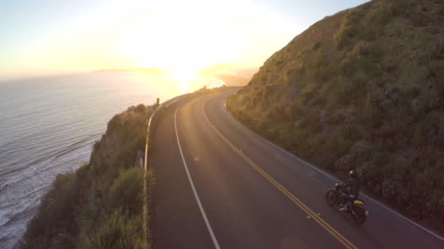 Motorbike driving on a highway by the coast during a stunning sunset in California Motorbike driving on a highway by the coast during a stunning sunset in California motorcycle stock videos & royalty-free footage