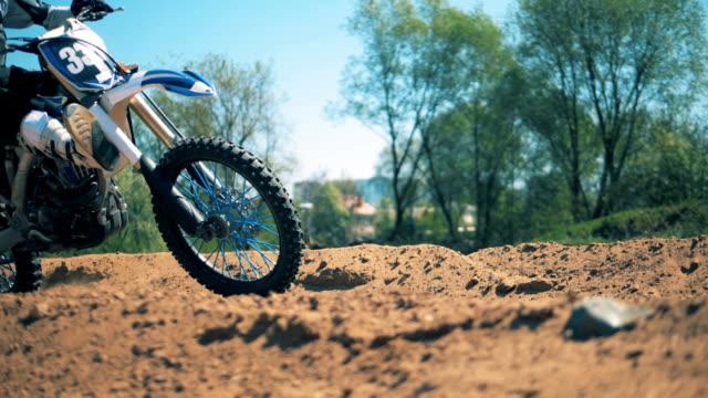 la moto corre su terreni sabbiosi al rallentatore - supercross video stock e b–roll