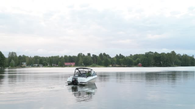 Motorboat Cruising In The Lake Against View Of Nature