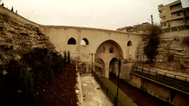 Motorcycle Crosses Old Bridge under Ancient Canal in Sanliurfa Bottom View Cloudy Wintry Day video