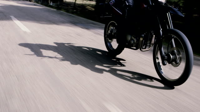 Motorcycle moving along the asphalt street. Front wheel close up