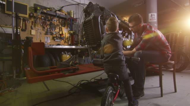 officina di riparazione moto - garage video stock e b–roll