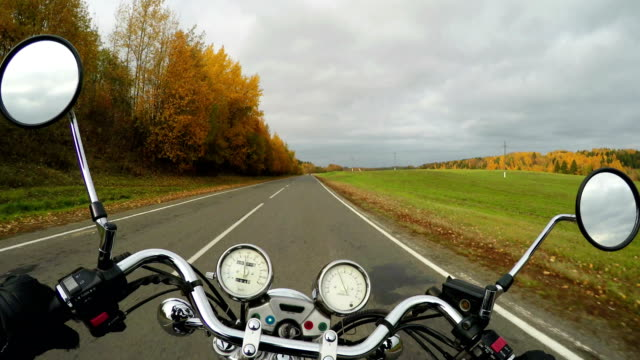 4K. Motorcycle rides on the beautiful autumn road at sunny day, wide point of view of rider. Classic cruiser/chopper forever!