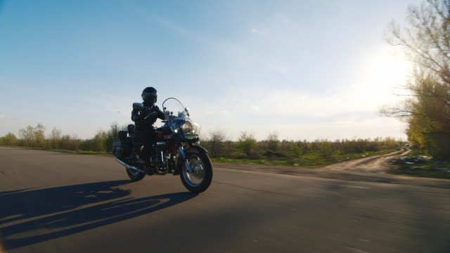 Motorcycle riding on a country road, the sun shines on it Shooting from the lowest point, accompanied by motorcycle - biker on country road motorcycle stock videos & royalty-free footage